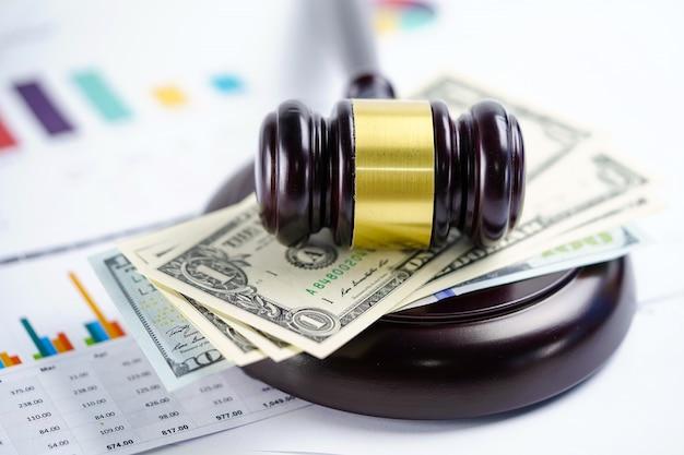 Молоток судьи с банкнотами доллара сша на миллиметровке диаграммы.