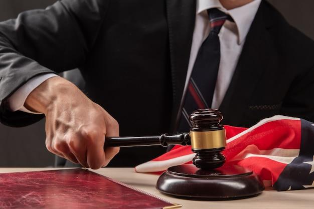 판사는 망치로 테이블을 친다. 법정에서 판사는 변호사에게 유죄를 선고했습니다. 판사의 망치를 손에 닫습니다.