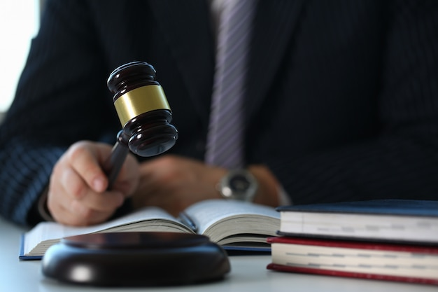 Судья, держащий молоток в руке, лежит на столе в комнате для дискуссий для справедливого суждения экономических представлений о нарушениях правовой системы мошенничества и наказания