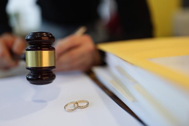 Судья держит деревянный молоток возле двух обручальных колец крупным планом