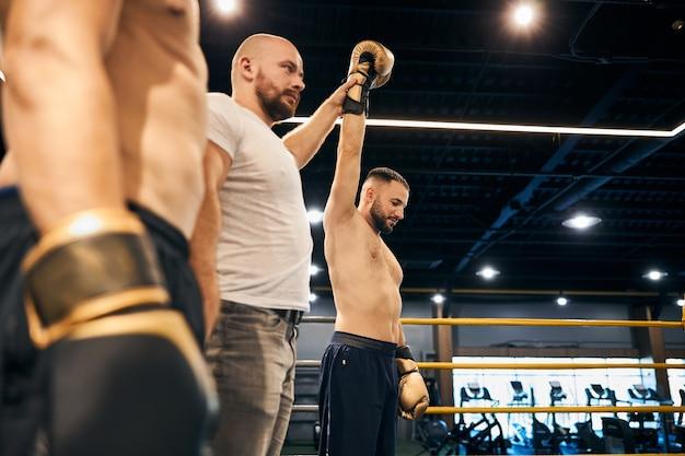 Судья в белой рубашке поднимает руку чемпиона, объявляя о его победе