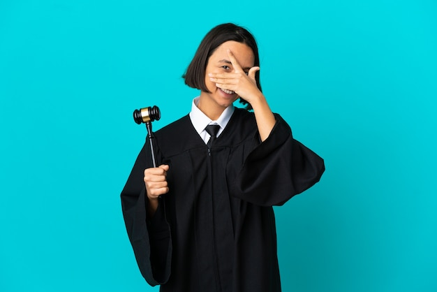Judge over isolated blue background covering eyes by hands and smiling