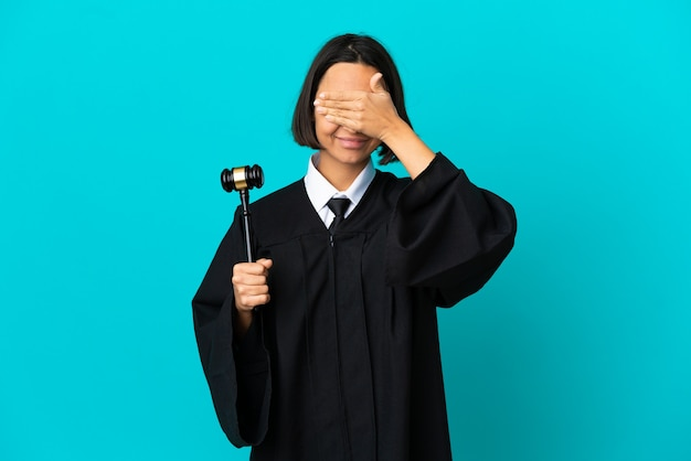Judge over isolated blue background covering eyes by hands