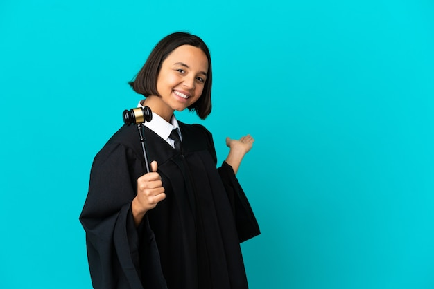 Judge over isolated blue background extending hands to the side for inviting to come
