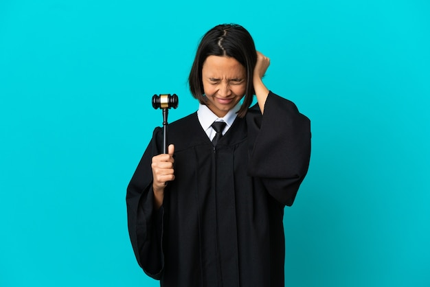 Judge over isolated blue background frustrated and covering ears