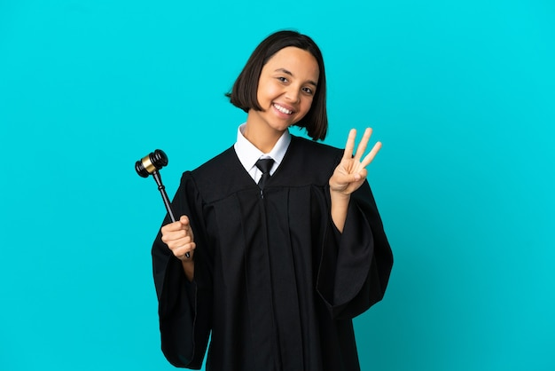 Judge over isolated blue background happy and counting three with fingers