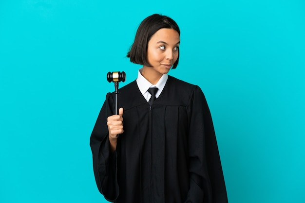 Judge over isolated blue background having doubts while looking up