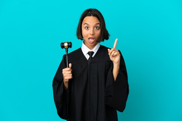 Judge over isolated blue background intending to realizes the solution while lifting a finger up