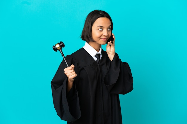 Judge over isolated blue background keeping a conversation with the mobile phone with someone