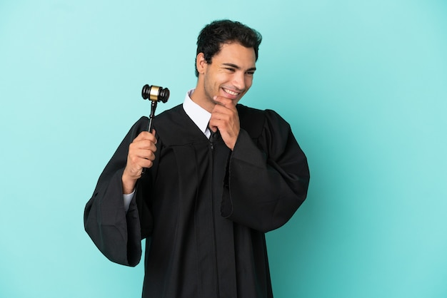 Judge over isolated blue background looking to the side and smiling