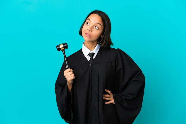 Judge over isolated blue background looking up while smiling