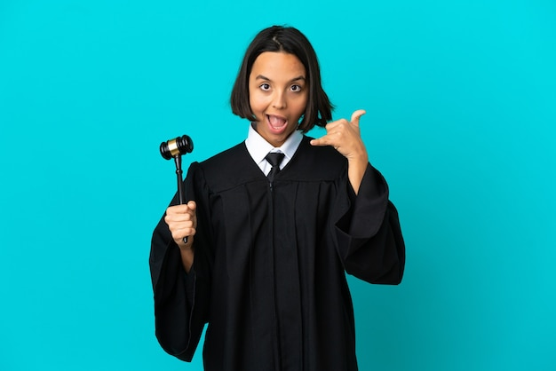 Judge over isolated blue background making phone gesture. call me back sign