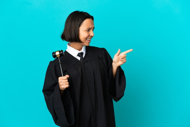 Judge over isolated blue background pointing finger to the side and presenting a product
