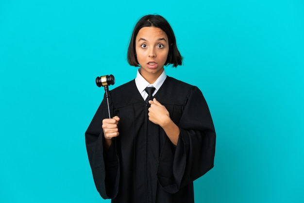 Judge over isolated blue background pointing to oneself