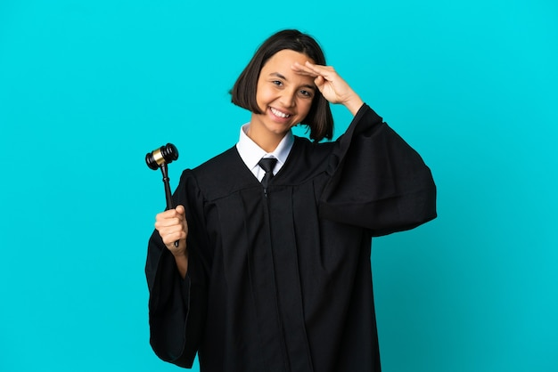 Judge over isolated blue background saluting with hand with happy expression