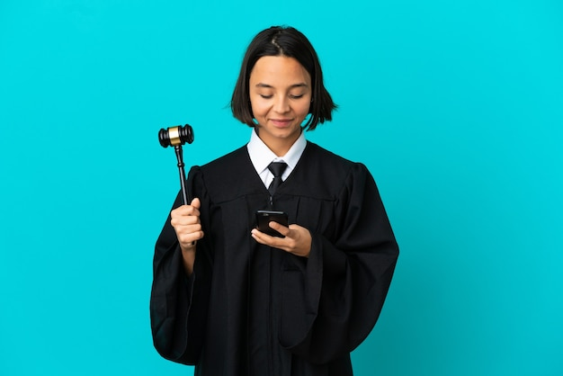 Judge over isolated blue background sending a message with the mobile