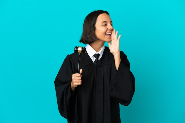 Judge over isolated blue background shouting with mouth wide open to the side