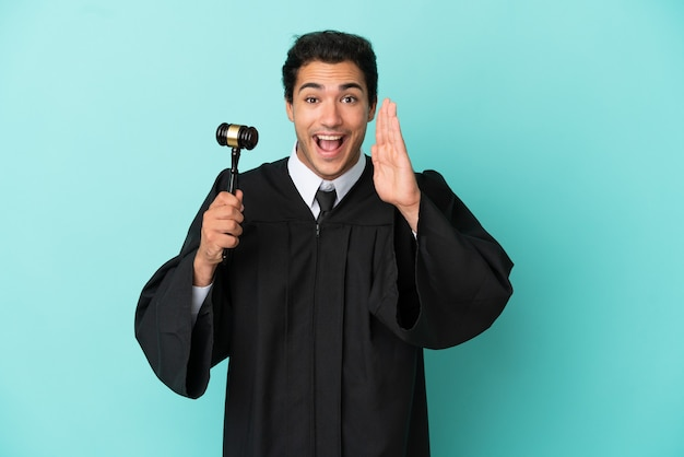Judge over isolated blue background shouting with mouth wide open