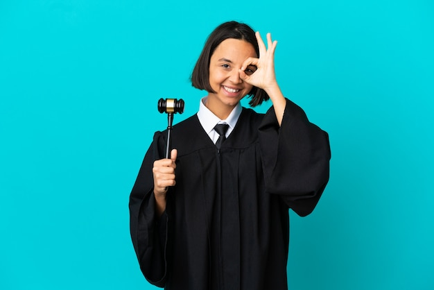 Judge over isolated blue background showing ok sign with fingers