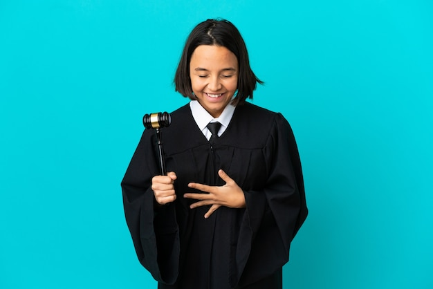 Judge over isolated blue background smiling a lot