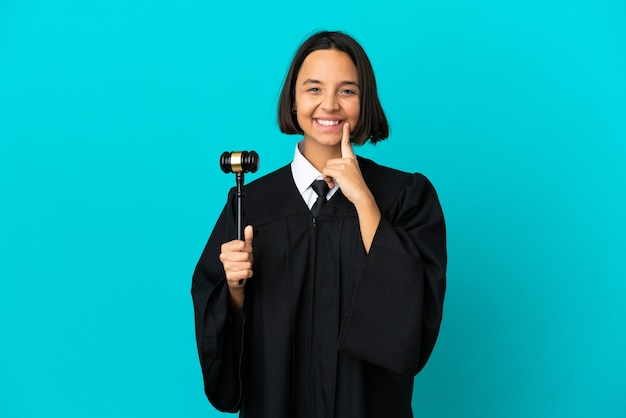 Judge over isolated blue background smiling with a happy and pleasant expression