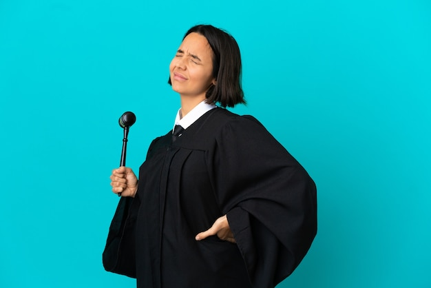 Judge over isolated blue background suffering from backache for having made an effort