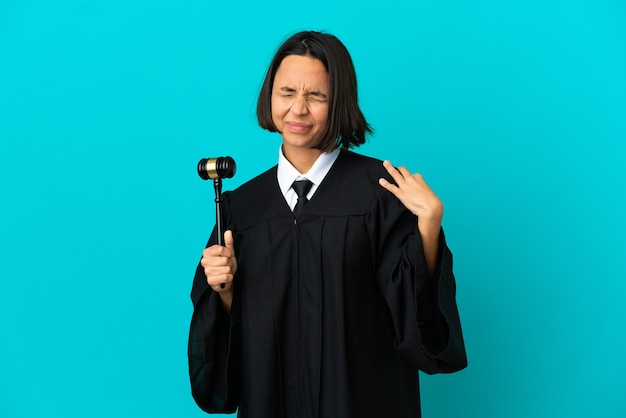 Judge over isolated blue background suffering from pain in shoulder for having made an effort