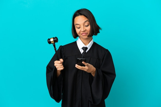 Judge over isolated blue background thinking and sending a message