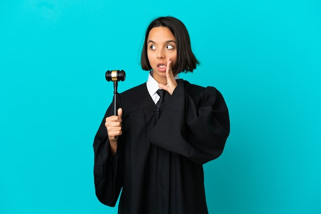 Judge over isolated blue background whispering something with surprise gesture while looking to the side