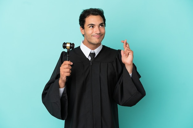 Judge over isolated blue background with fingers crossing and wishing the best