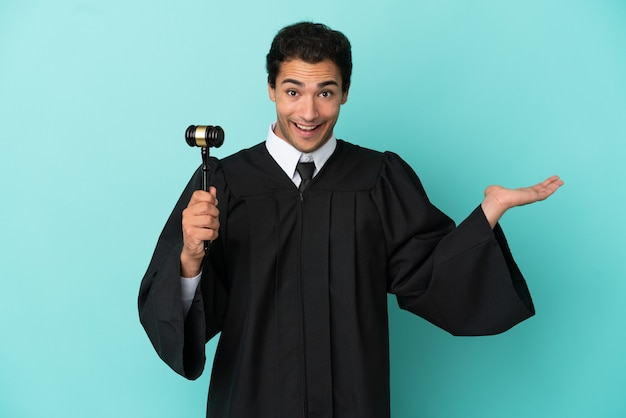 Judge over isolated blue background with shocked facial expression