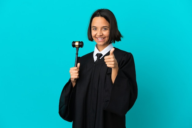 Judge over isolated blue background with thumbs up because something good has happened