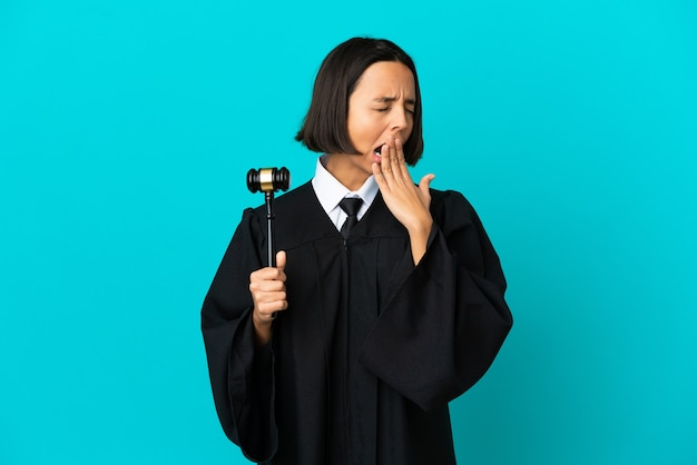 Judge over isolated blue background yawning and covering wide open mouth with hand