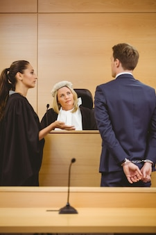 Judge and lawyer listening the criminal in handcuffs in the court room