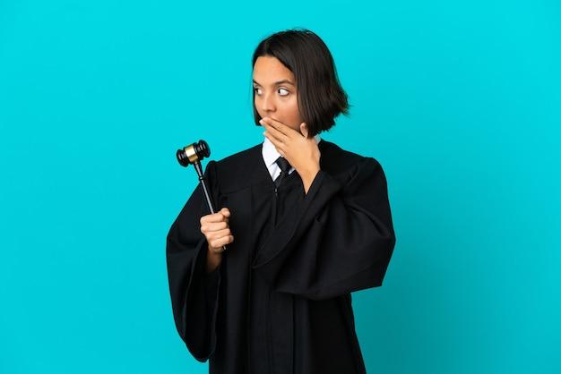 Судья на изолированном синем фоне делает неожиданный жест, глядя в сторону
