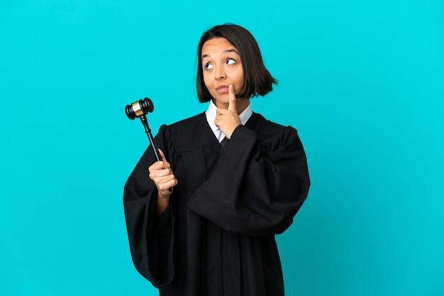 올려다보는 동안 의심을 품고 고립된 파란색 배경 위에 판사