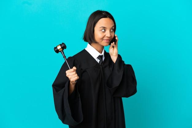 다른 사람과 휴대 전화로 대화를 유지하는 고립 된 파란색 배경 위에 판사