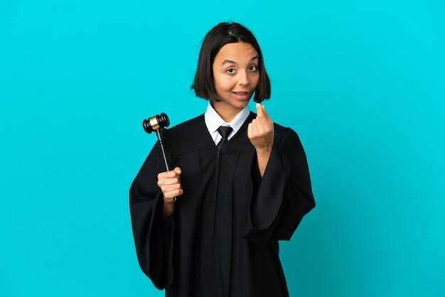 Судья на изолированном синем фоне, делая денежный жест