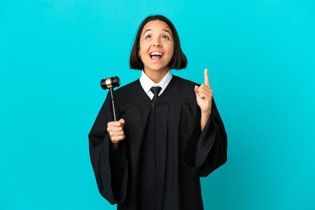 위를 가리키고 놀란 고립된 파란색 배경 위에 판사
