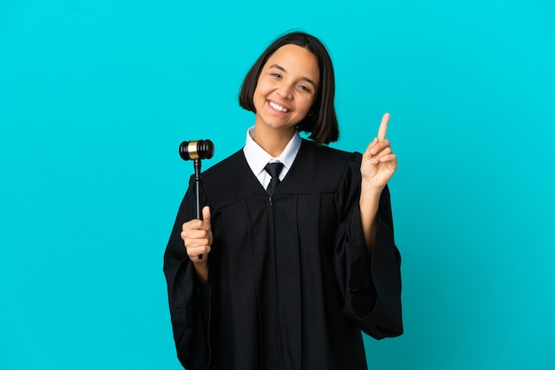 Судите над изолированным синим фоном, показывая и поднимая палец в знак лучших