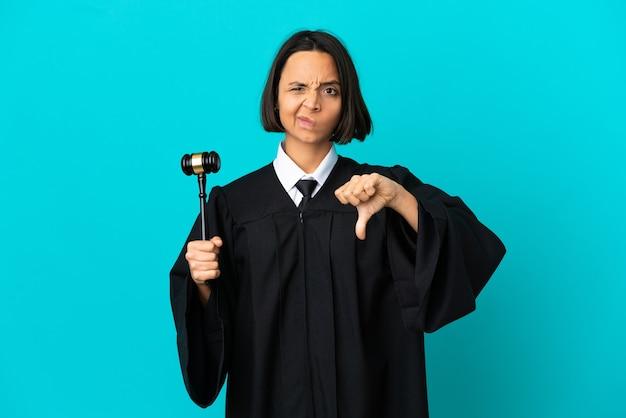 부정적인 표정으로 엄지손가락을 아래로 보여주는 격리된 파란색 배경 위에 판사