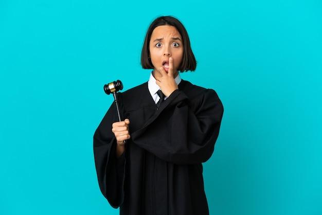 격리된 파란색 배경 위에 있는 판사는 오른쪽을 보고 놀라고 충격을 받았습니다.
