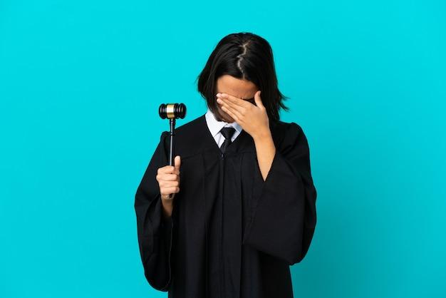 Судите над изолированным синим фоном с усталым и больным выражением лица