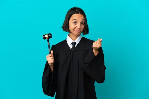 Судья над изолированной синей стеной, делая денежный жест
