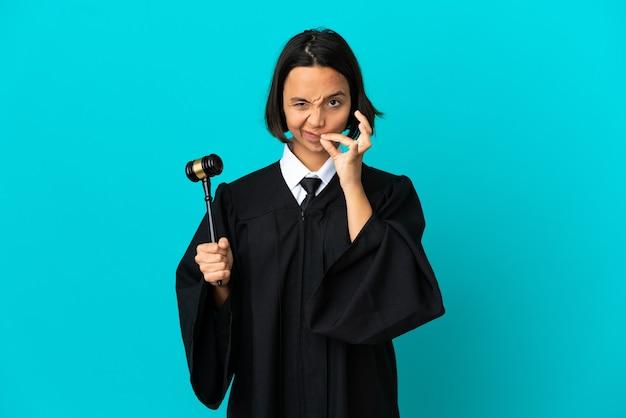 Судья над изолированной синей стеной показывает знак жеста молчания