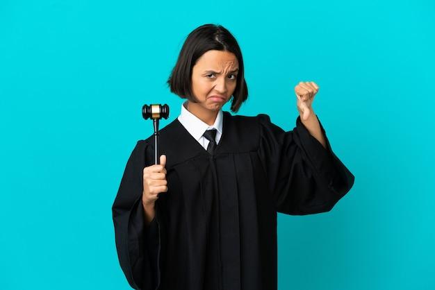 부정적인 표정으로 엄지손가락을 아래로 보여주는 고립된 파란색 벽 위에 판사