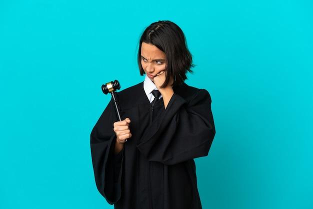 피곤하고 지루한 표정으로 고립 된 파란색 벽에 판사