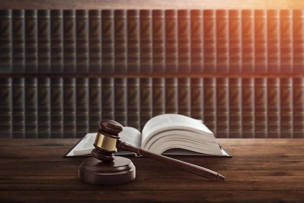 Молоток судьи и книга на деревянном столе.