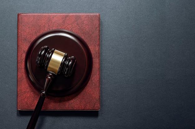 裁判官のガベルと黒い革の背景、上面図の本。法律の概念。