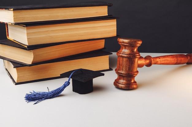 테이블에 책과 함께 판사의 망치와 졸업 모자.